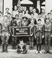 Carpinteria Boy Scout Troop with Kenji and Tom Ota in front of Carpinteria Union School : 1926. Kenji left of banner, Tom directly behind banner.