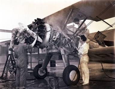 Women performing maintenance on a PT-13 Stearman trainer, Hancock College of Aeronautics