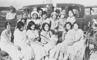 Christening party for Adeline Cabreana, Guadalupe Produce Labor Camp, Lompoc : 1932. Seated L-R: Margarita Bautista, unidentified, Maria Salutan, Mati holding the baptized Adeline, Maria Tenequez Cabreana, and Margarita Cabatuan. Standing: Maria Putin, Insay Mansalvas, Justa Abenida, unidentified, Maria Completo, and Bernalda Tenequez. In the driver's seat: Sarapio Cabatuan, nearest car; Santiago Salutan, distant car.