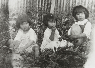 James Ezaki, Ruth Soko Ezaki and William Ezaki aged between 2 and 4 years, sitting in a watermelon patch, Carpinteria : 1909.