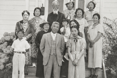 Japanese Methodist Church, A Street, Oxnard : 1937. Clockwise from far left around outside: Calvin Machida, Mrs. Yasuye Takasugi, Mrs. Machida, Rev. K Babu (founder and first minister of church), Mrs. Yamada, Faye Hirata, Tsuruka Yamada, Mrs. Kawata, Mrs. Mano & Mr. Mano. In middle on left: Mrs. Otani (wearing hat), woman holding child not identified.