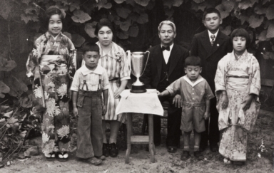 The Moriwaki Family of Oxnard: about 1934 ; back L-R: Masako, Masano (mother), Tokutaro (father), Norio ; Front: Noriyoshi, Takanori, Masami ; the trophy was presented to Mr. Moriwaki when he was President of Oxnard Buddhist Church.