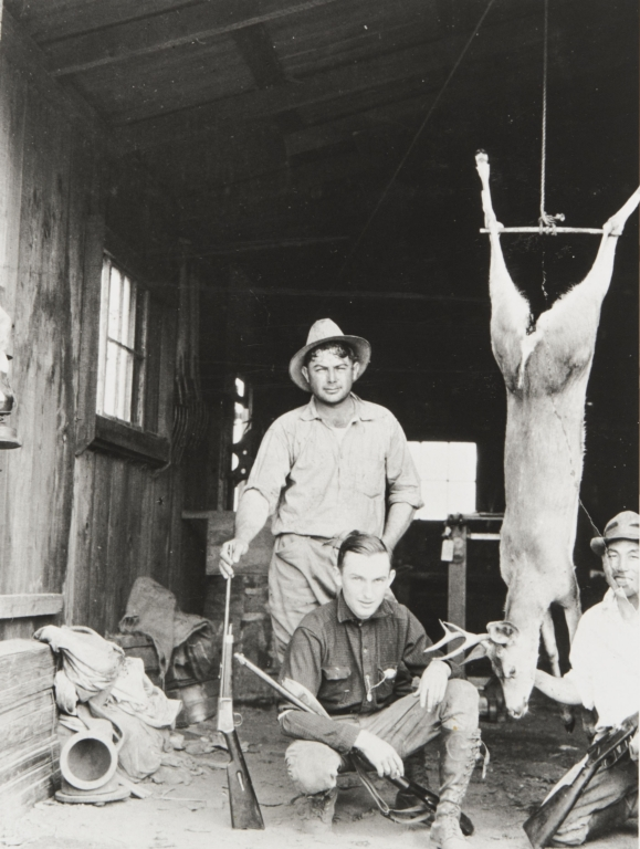 """Al Silva, Art Marshall and Yoshio """"George"""" Nagano after successful hunt. Morro Bay : 1927. Note abalone diving gear and helmet on floor."""