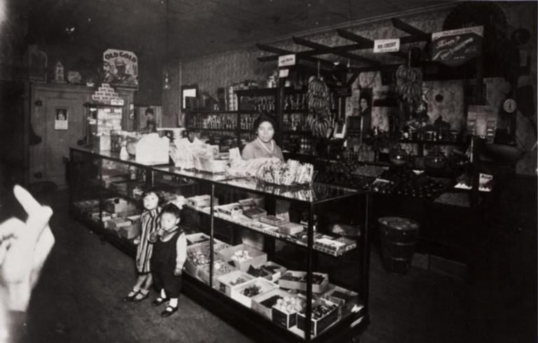 T. Moriwaki Store : 716 Oxnard Boulevard, Oxnard : 1931 ; Masano Moriwaki behind showcase ; children Masami and Noriyoshi.