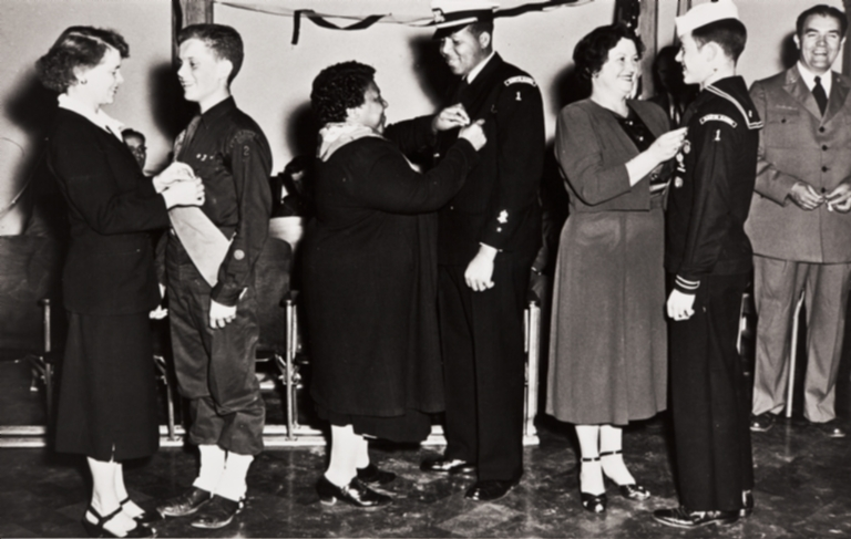 Eulamae Whiteside Gatewood pinning Eagle Scout badge on Leander Gatewood, Santa Maria's first black Eagle Scout, at a meeting of the Sea Explorer Scouts at the American Legion Hall in 1950.