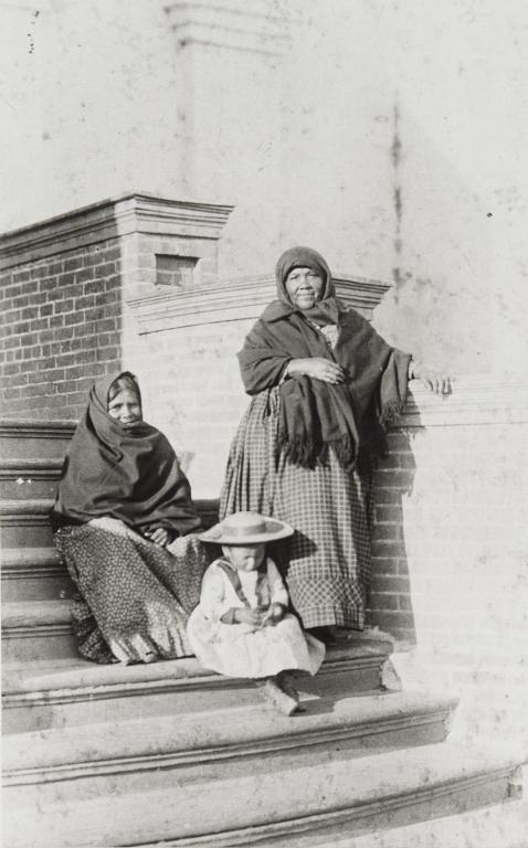 Ventureño Chumash women, Apolonia Guzman (left) and Petra Pico (right). The child seated on the steps is Petra's great granddaughter, Soraida García : ca. 1888.