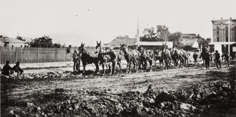 Plowing up State Street, First National Bank at right : 1887.