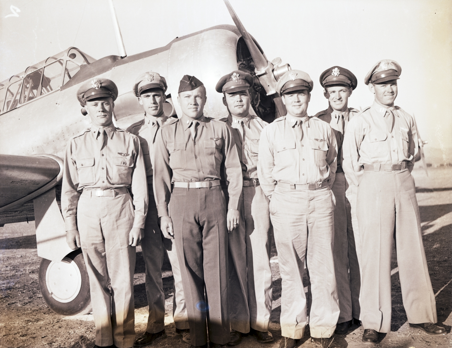 Flight instructors posing in front of a training aircraft, Hancock College of Aeronautics