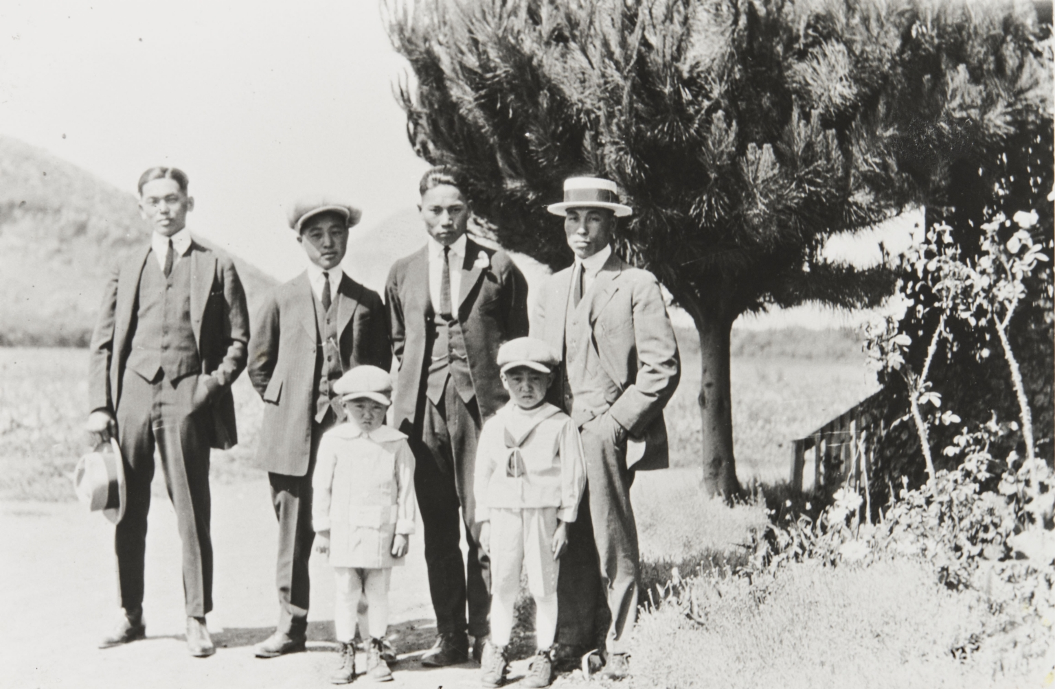 "Three Japanese farm workers with Yoshio ""George"" Nagano and sons Patrick and William. Nagano Farm, Morro Bay : 1922."