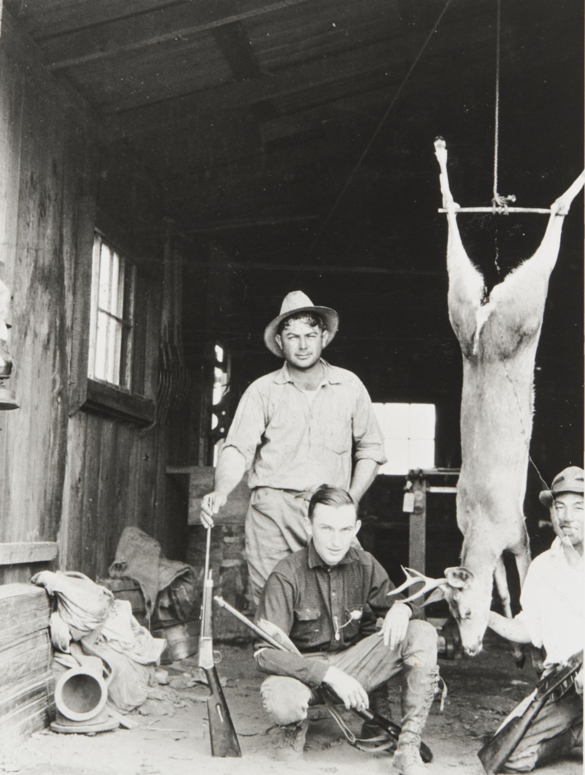 "Al Silva, Art Marshall and Yoshio ""George"" Nagano after successful hunt. Morro Bay : 1927. Note abalone diving gear and helmet on floor."